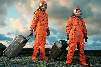 People walking in space suits with luggage.